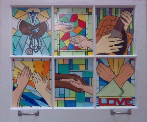 """A Window Into Hospice,"" by Tammy Hromadka. Six panels set in an old window frame, each showing the hands of a caregiver."